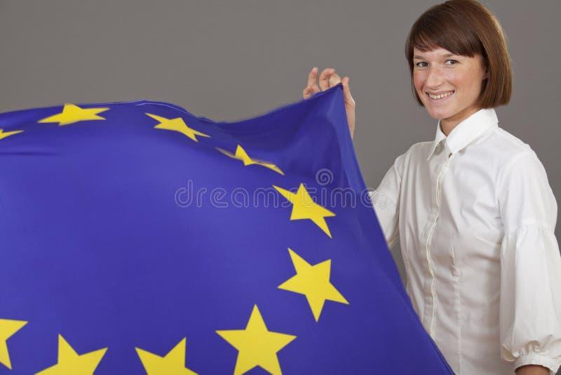 Glückliche Frau, die europäische Markierungsfahne anhält lizenzfreie stockfotos