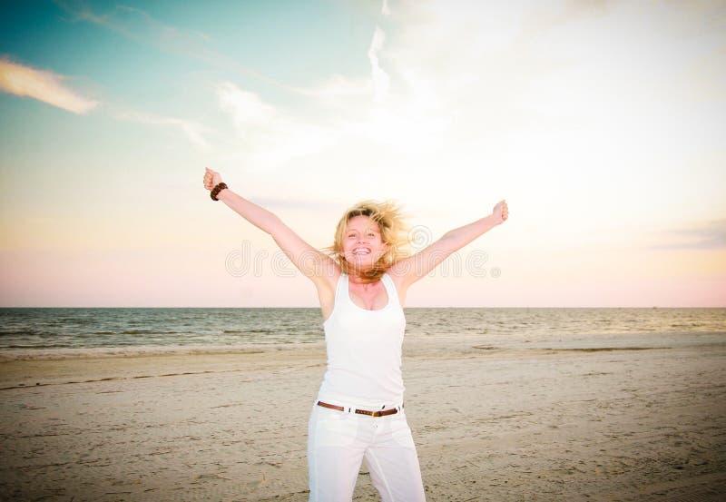 Glückliche Frau, die für Freude springt stockfotos