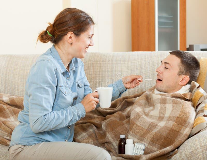 Glückliche Frau, die für kranken Ehemann sich interessiert stockbild