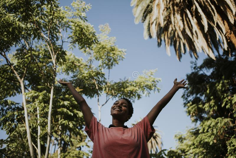 Glückliche Frau, die frei in den Park glaubt stockfotografie