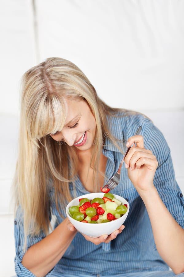 Glückliche Frau, die frischen Obstsalat isst lizenzfreies stockfoto