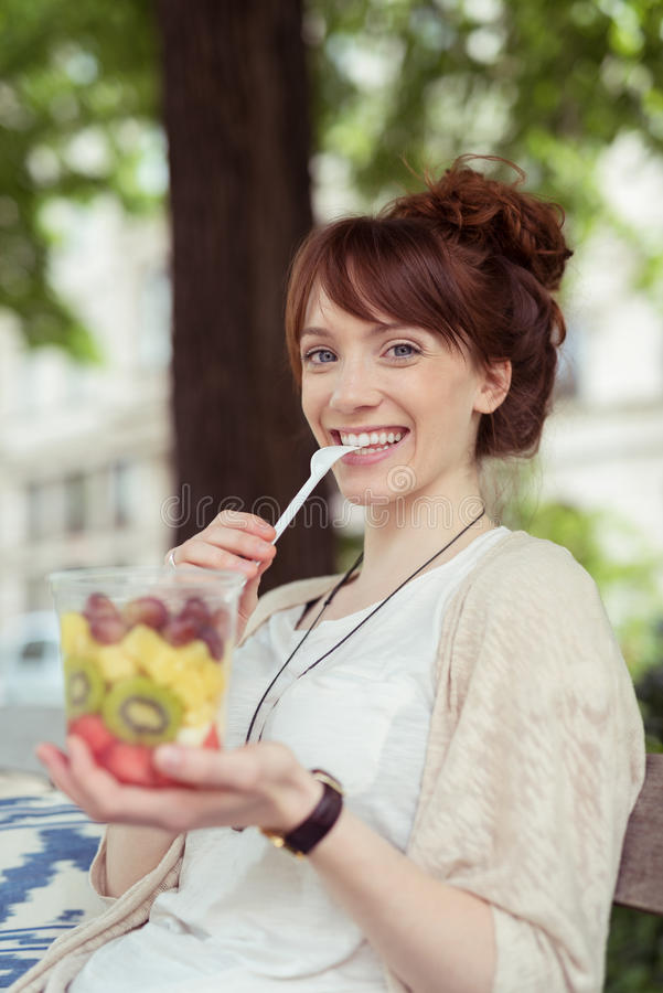 Glückliche Frau, die frischen Obstsalat isst lizenzfreies stockbild