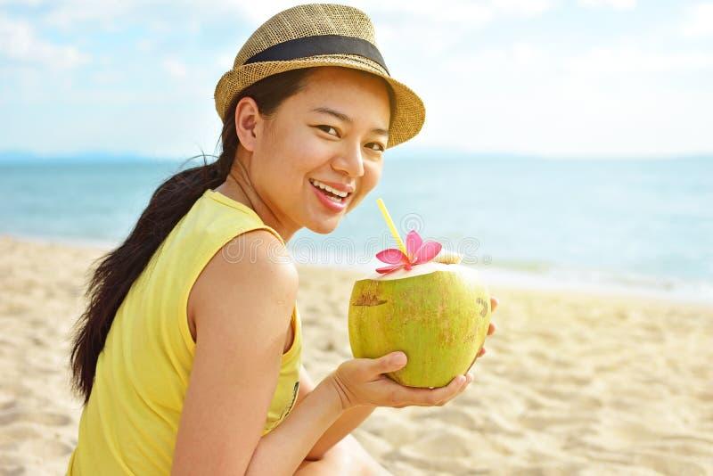 Glückliche Frau, die frisches Kokosnusswasser auf dem Strand trinkt stockbilder