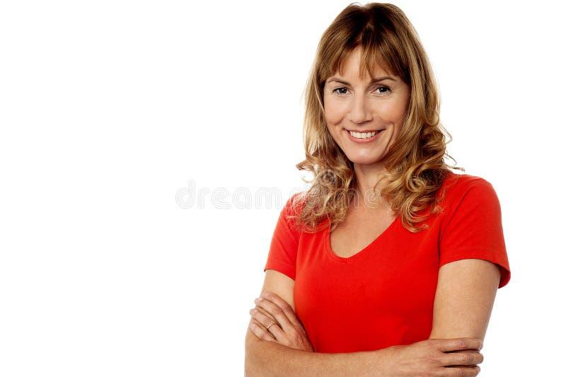 Glückliche Frau, die gegen Weiß steht lizenzfreies stockfoto