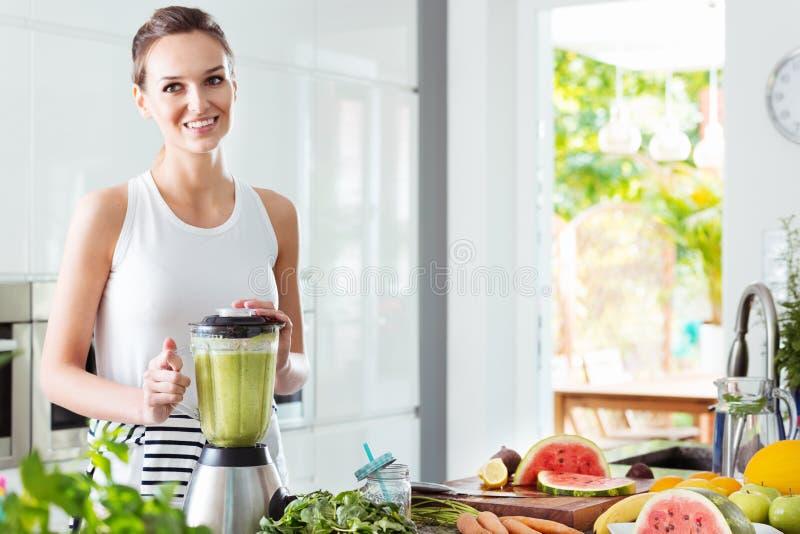 Glückliche Frau, die grünes Gemüse mischt lizenzfreie stockbilder