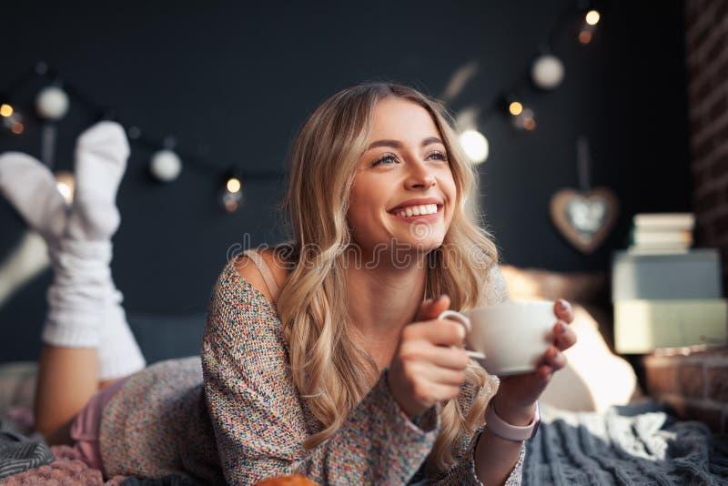 Glückliche Frau, die heißes Getränk auf Bett hat stockbilder
