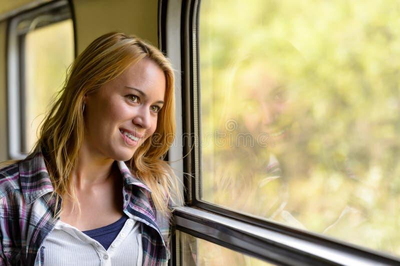 Glückliche Frau, die heraus das Serienfenster nachdenklich schaut stockfoto