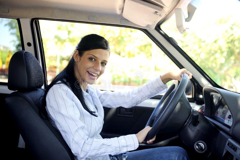 Glückliche Frau, die ihr neues Auto antreibt stockbilder