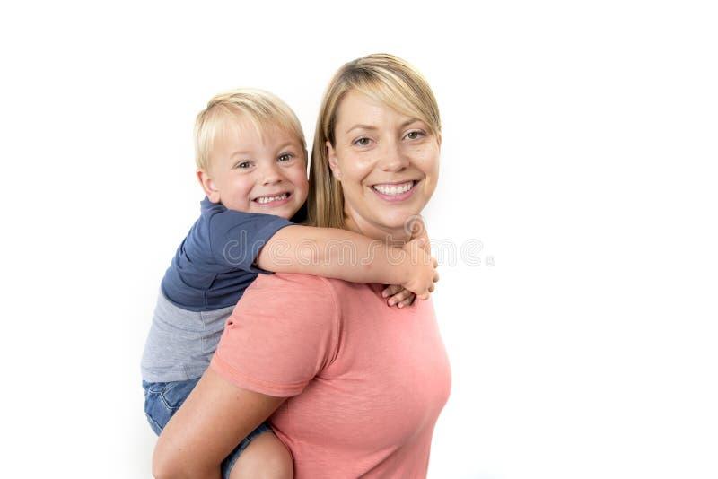 Glückliche Frau, die ihre entzückenden 3 Jahre alte kleine Jungen auf ihrem zurück zusammen lächeln glücklich und nett in der Fam stockfotografie