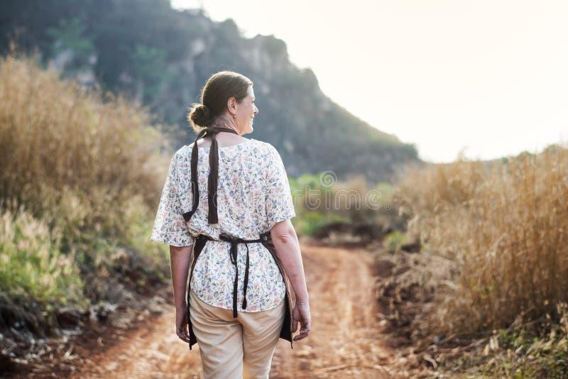 Glückliche Frau, die an ihrem Bauernhof geht lizenzfreies stockbild