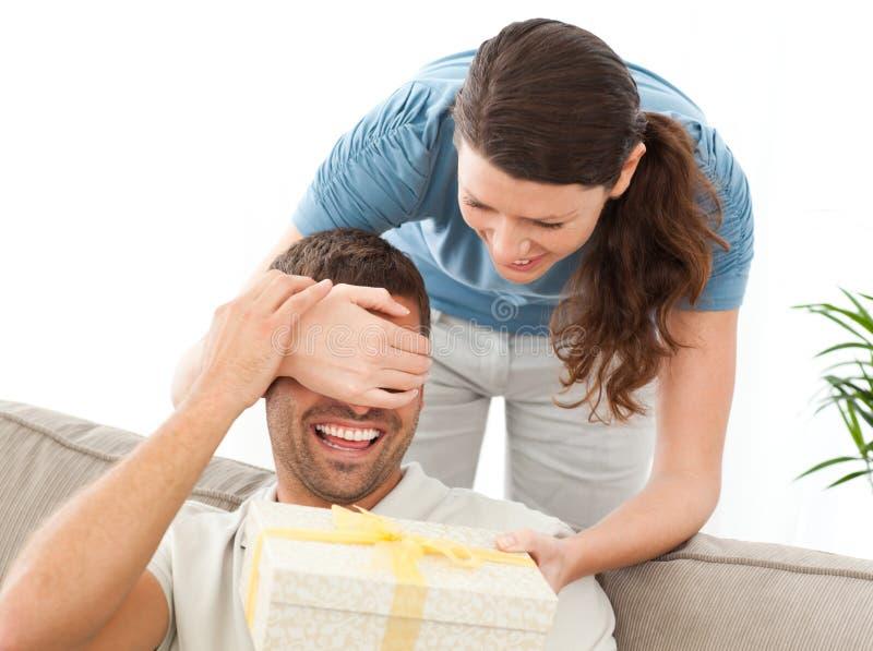 Glückliche Frau, die ihrem Ehemann ein Geschenk gibt stockfotos