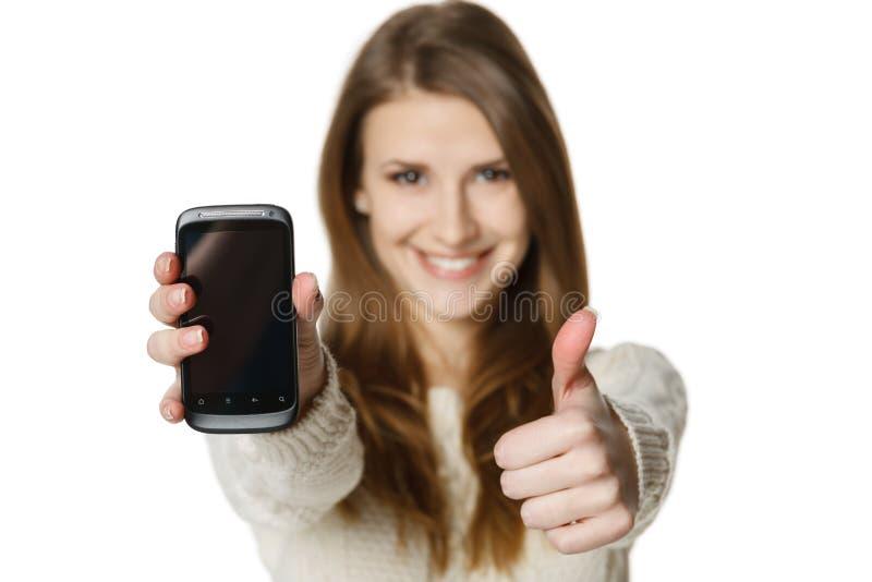 Glückliche Frau, die ihren Handy zeigt und oben Daumen gestikuliert lizenzfreie stockfotografie