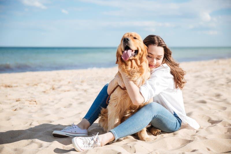 Glückliche Frau, die ihren Hund auf dem Strand sitzt und umarmt stockbild
