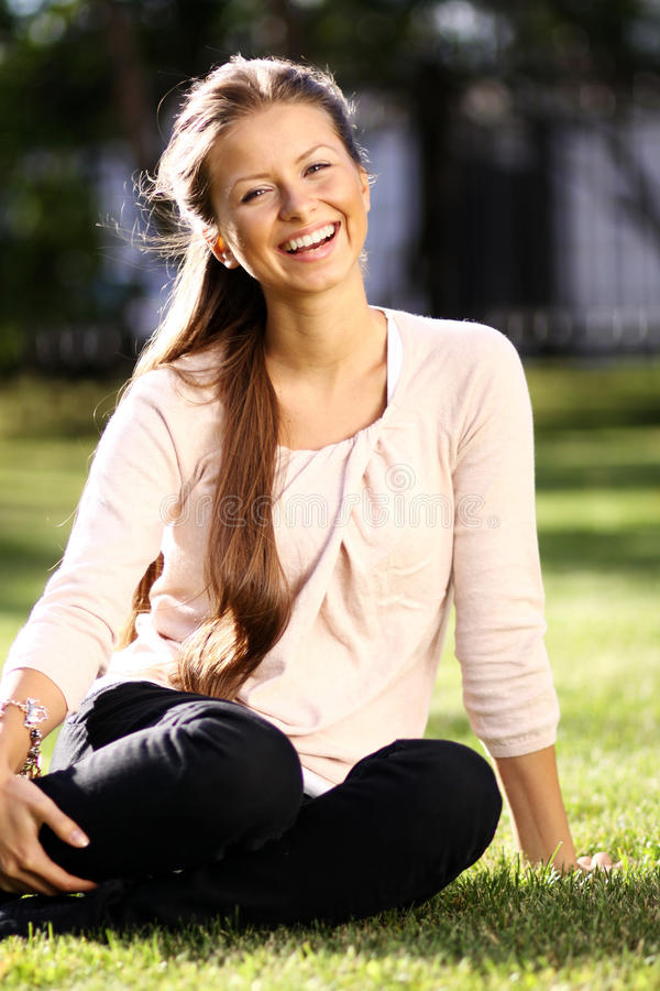 Glückliche Frau, die im Gras sich entspannt stockfotografie