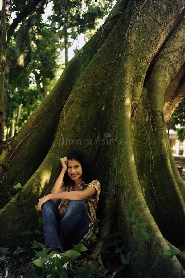 Glückliche Frau, die im Schatten eines Baums sitzt lizenzfreie stockfotografie