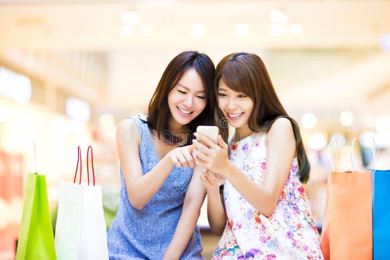 Glückliche Frau, die intelligentes Telefon auf Einkaufszentrum betrachtet stockbild