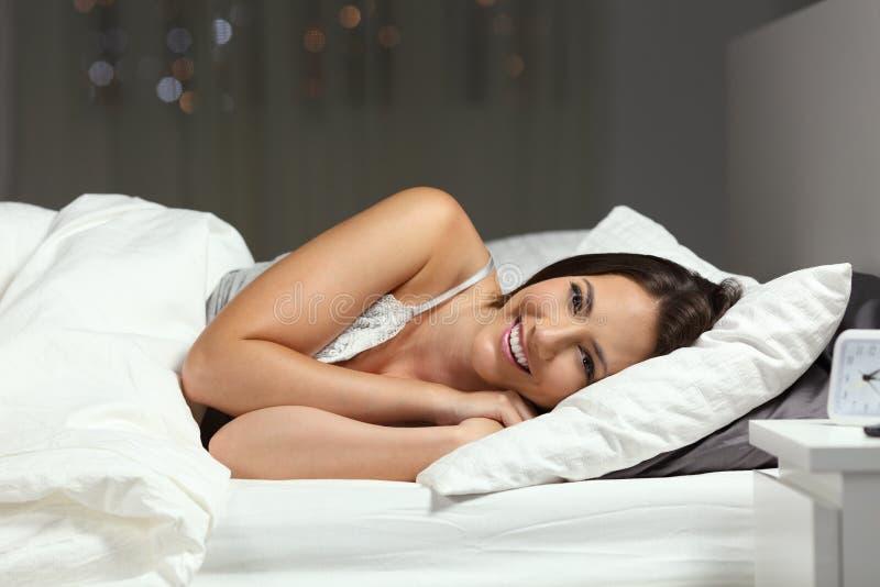 Glückliche Frau, die Kamera auf einem Bett in der Nacht betrachtet lizenzfreie stockbilder