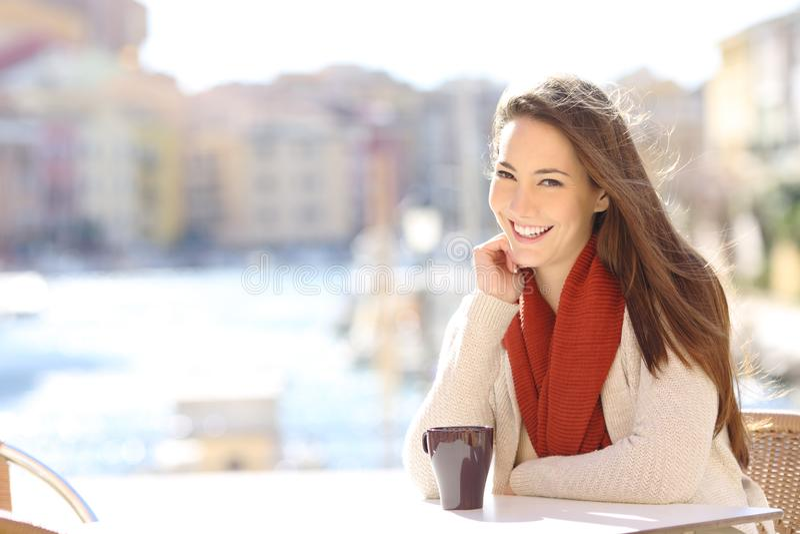 Glückliche Frau, die Kamera in einer Kaffeestube eines Hafens betrachtet lizenzfreies stockfoto