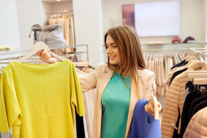 Glückliche Frau, die Kleidung am Bekleidungsgeschäft wählt lizenzfreie stockfotografie
