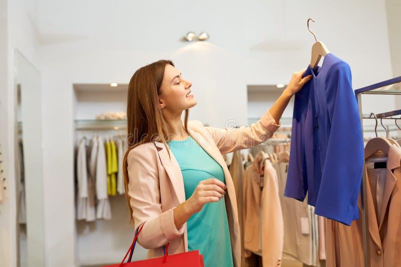 Glückliche Frau, die Kleidung am Bekleidungsgeschäft wählt stockfotografie