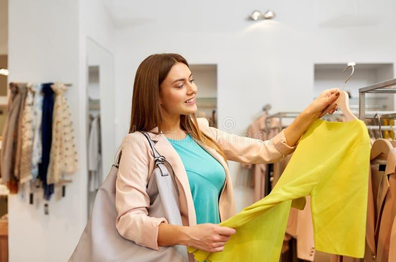 Glückliche Frau, die Kleidung am Bekleidungsgeschäft wählt lizenzfreies stockfoto