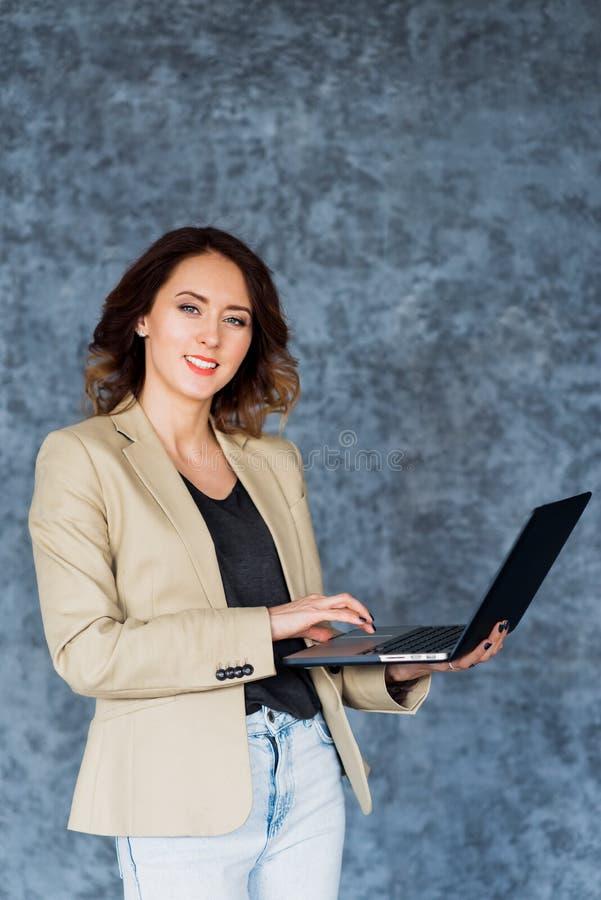 Glückliche Frau, die Laptop hält und an der Kamera über grauem Hintergrund lächelt lizenzfreie stockfotografie