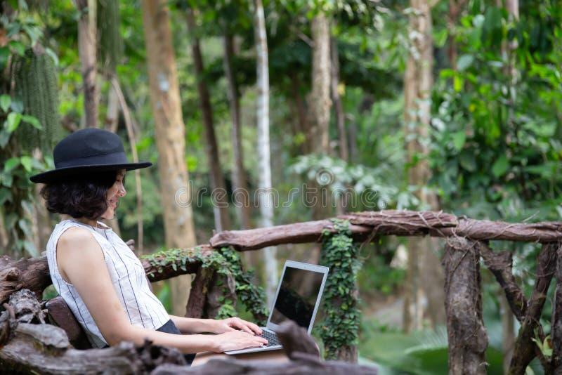 Glückliche Frau, die Laptop im Wald verwendet lizenzfreies stockfoto