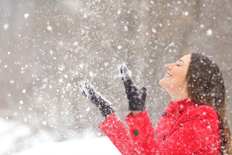 Glückliche Frau, die mit dem Schnee auf Winterurlaub spielt stockfotos