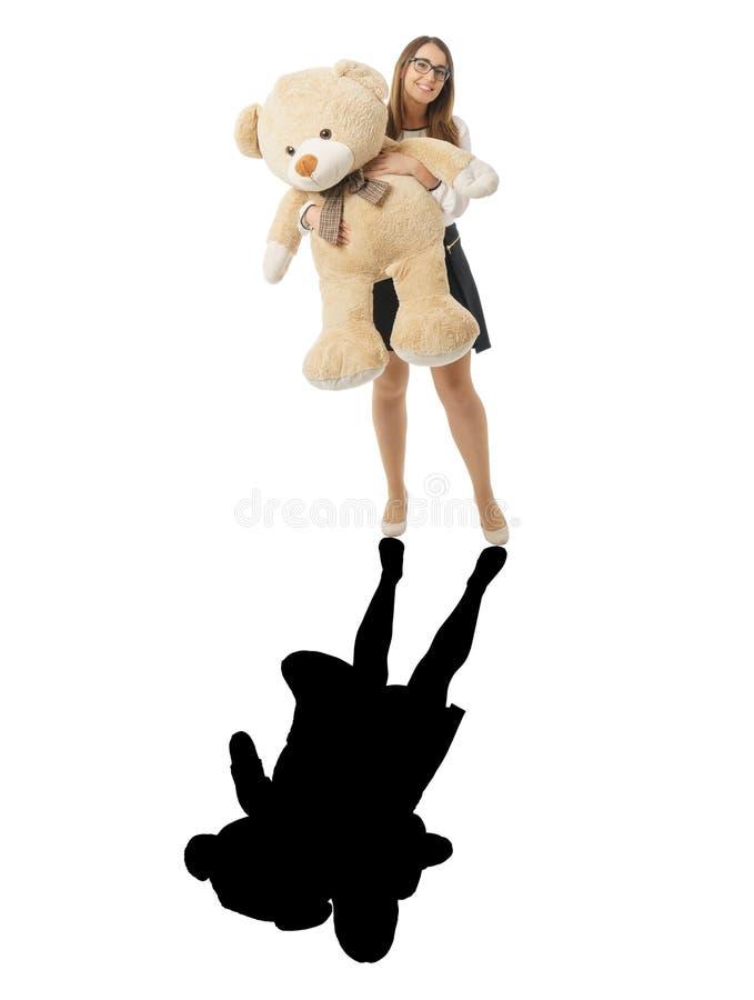 Glückliche Frau, die mit enormem Teddybären und schwarzem Schatten spielt stockbild