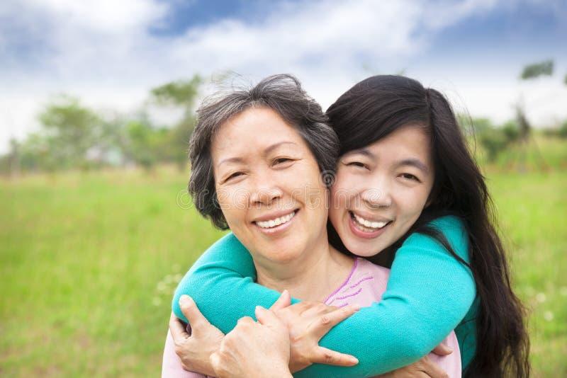 Glückliche Frau, die mit ihrer Mutter umarmt stockfotos