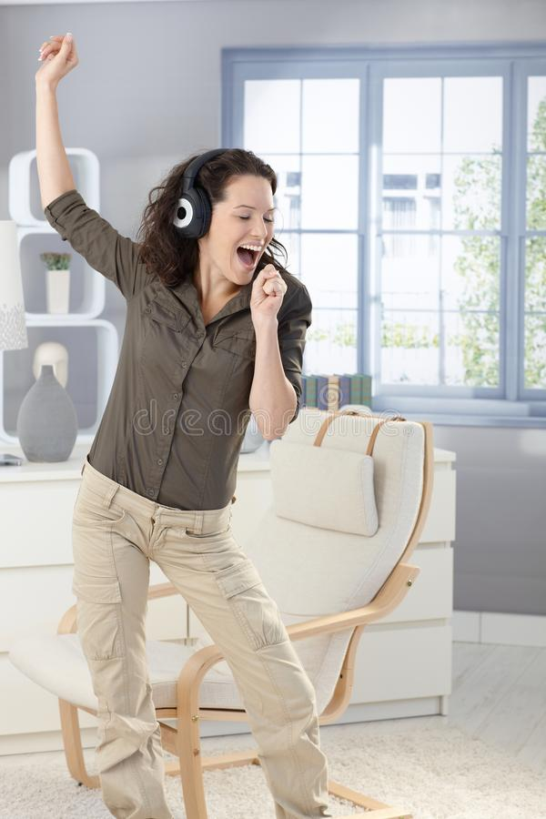 Glückliche Frau, die mit Kopfhörern singt lizenzfreie stockfotografie