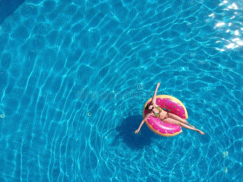 Glückliche Frau, die mit in Pool mit Donutmatratze sich entspannt stockfoto