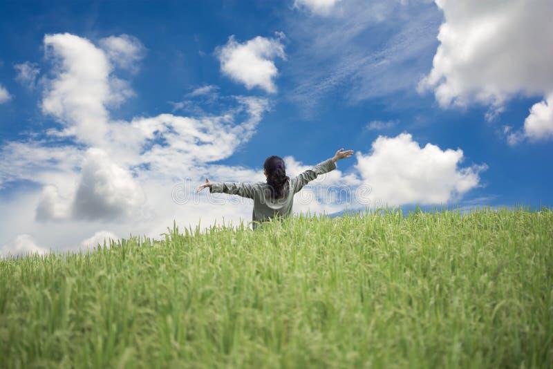 Glückliche Frau, die mitten in dem Feld steht lizenzfreie stockfotografie