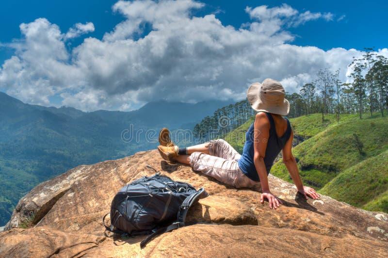 Glückliche Frau, die Natur auf Gebirgsklippe genießt stockbild