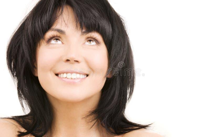 Glückliche Frau, die oben über Weiß schaut stockfotografie