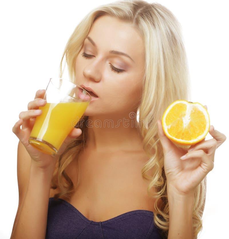 Glückliche Frau, die Orangensaft trinkt. lizenzfreies stockfoto