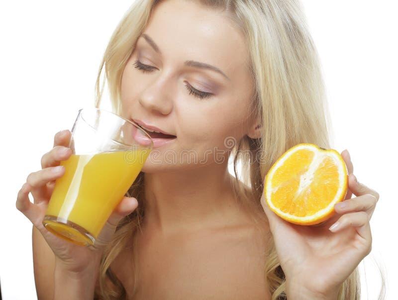 glückliche Frau, die Orangensaft trinkt. stockfotografie