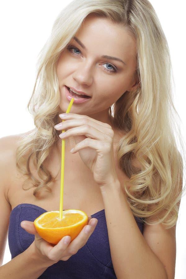 Glückliche Frau, die Orangensaft trinkt. stockfoto