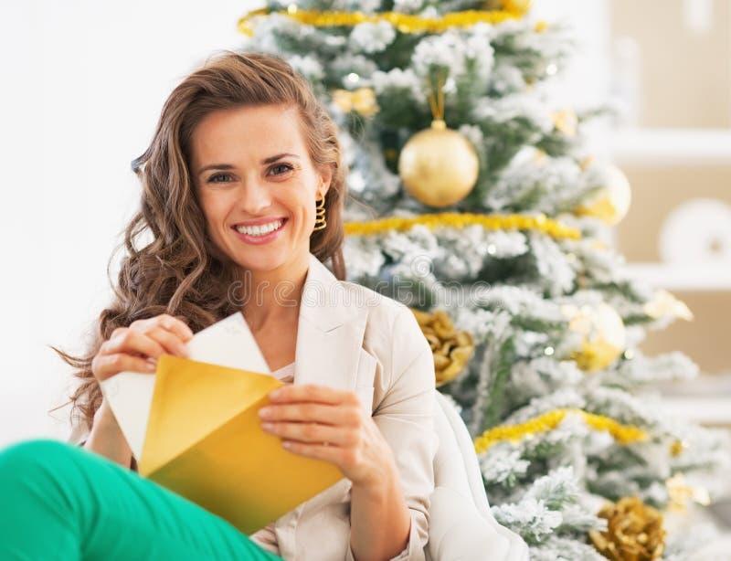 Glückliche Frau, die Postkarte in Umschlag nahe Weihnachtsbaum setzt stockbilder