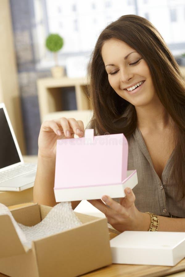 Glückliche Frau, die Postpaket öffnet lizenzfreies stockfoto