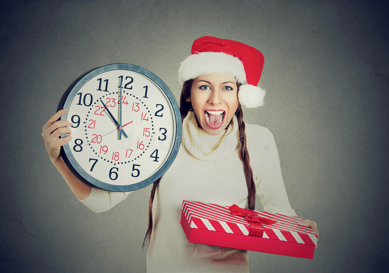 Glückliche Frau, die roten Weihnachtsmann-Hut hält Uhrgeschenkbox trägt stockbilder