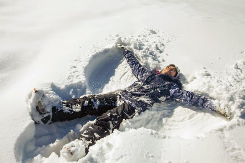 Glückliche Frau, die Schneeengel im Schnee macht stockfotografie