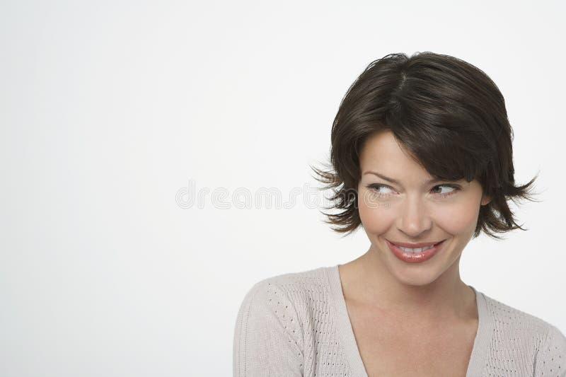Glückliche Frau, die seitlich flüchtig blickt lizenzfreie stockfotografie