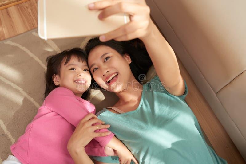 Glückliche Frau, die selfie mit Tochter nimmt lizenzfreie stockbilder