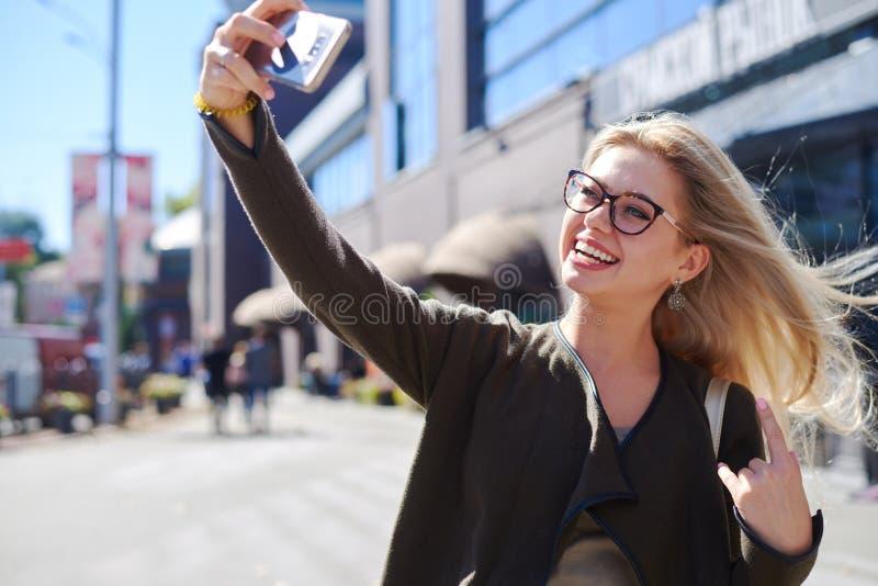 Glückliche Frau, die selfie unter Verwendung der beweglichen Kamera in der Stadt nimmt lizenzfreie stockfotos