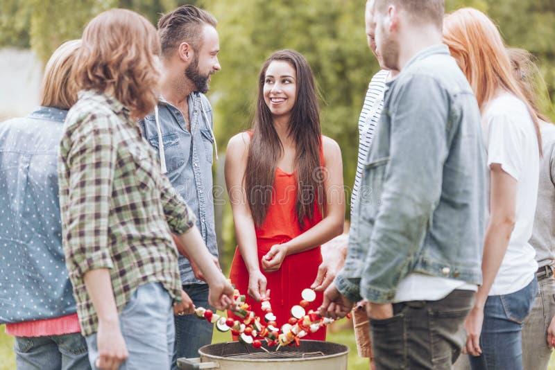 Glückliche Frau, die shashlik mit Freunden während der Geburtstagsfeier im Garten grillt stockfoto
