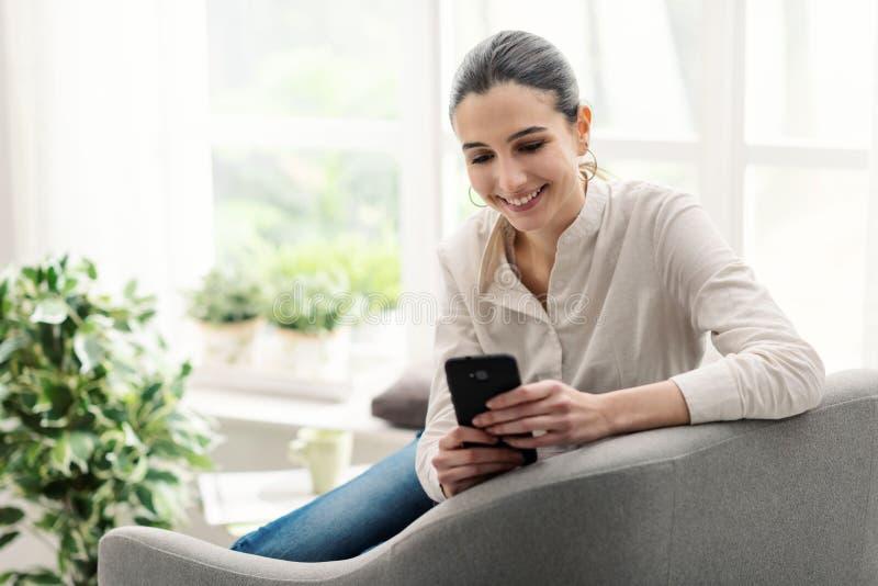 Glückliche Frau, die sich mit ihrem Smartphone verbindet lizenzfreie stockfotografie