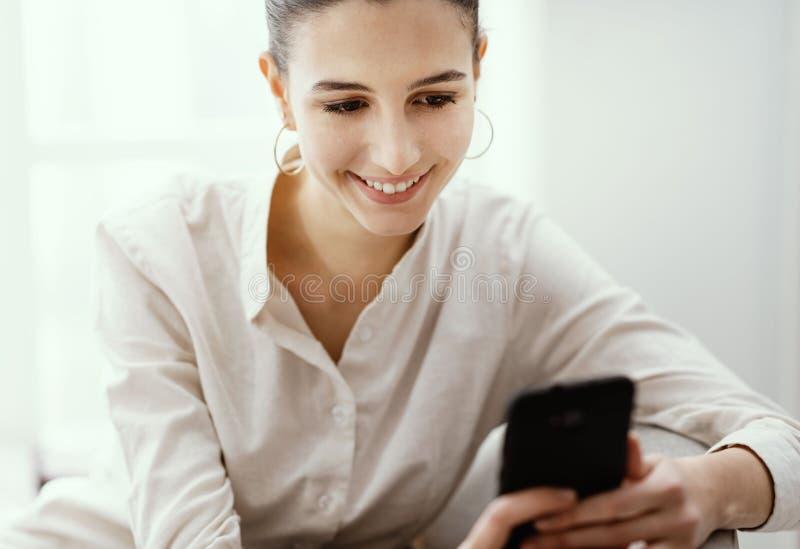 Glückliche Frau, die sich mit ihrem Smartphone verbindet lizenzfreie stockfotos