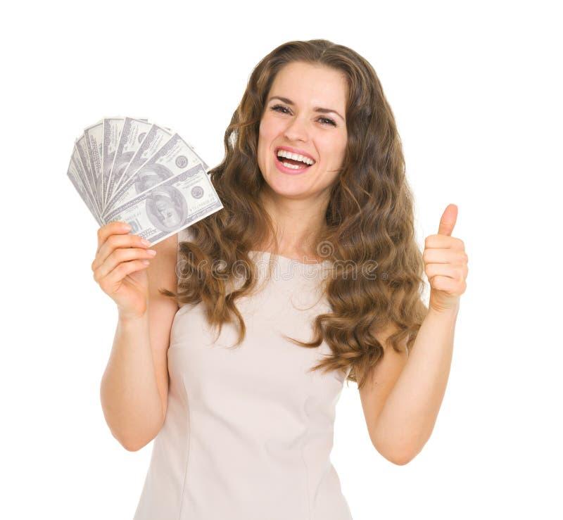 Glückliche Frau, die sich Spaß der Dollar und der Daumen zeigt stockfotografie