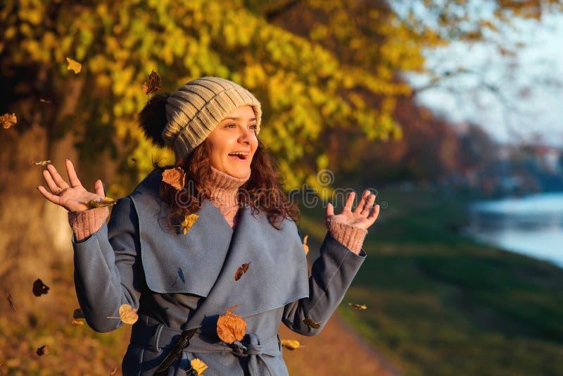 Glückliche Frau, die Spaß mit Herbstlaub draußen hat Frauenart und weise Autumn Time Junge Frau reist in Herbst Lebensstil, Leute stockbild